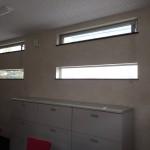 横長縦すべりで採光をとりつつ窓下に棚などを置くスペースを確保。